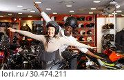 Купить «young couple having fun at motorcycle salon after buying new bike», фото № 30474211, снято 16 января 2019 г. (c) Яков Филимонов / Фотобанк Лори