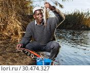 Man putting caught fish in bucket. Стоковое фото, фотограф Яков Филимонов / Фотобанк Лори