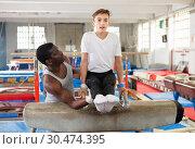 Купить «Male coach training teenage boy on gymnastic equipment at acrobatic hall», фото № 30474395, снято 17 января 2019 г. (c) Яков Филимонов / Фотобанк Лори
