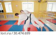 Athletic men training their aikido skills. A man grabs his opponent and throws him over. Стоковое видео, видеограф Константин Шишкин / Фотобанк Лори
