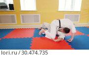 Athletic men training their aikido skills in the studio. Showing protection technique. Стоковое видео, видеограф Константин Шишкин / Фотобанк Лори