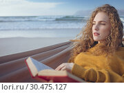 Купить «Woman holding book while lying on hammock at beach », фото № 30475127, снято 14 ноября 2018 г. (c) Wavebreak Media / Фотобанк Лори