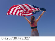 Купить «Young woman holding american flag at beach on sunny day», фото № 30475327, снято 14 ноября 2018 г. (c) Wavebreak Media / Фотобанк Лори
