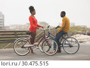 Купить «Couple interacting with each other while holding bicycle», фото № 30475515, снято 14 ноября 2018 г. (c) Wavebreak Media / Фотобанк Лори