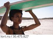 Купить «Young African American woman carrying the surfboard on her head at beach», фото № 30475827, снято 9 января 2019 г. (c) Wavebreak Media / Фотобанк Лори
