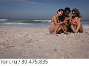 Купить «Happy young women using mobile phone while sitting at beach», фото № 30475835, снято 9 января 2019 г. (c) Wavebreak Media / Фотобанк Лори