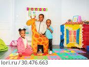 Купить «Group of black boys and girl hold drawn giraffe», фото № 30476663, снято 3 февраля 2019 г. (c) Сергей Новиков / Фотобанк Лори