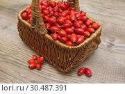 Купить «Rosehip berries in a basket on a wooden background», фото № 30487391, снято 21 сентября 2014 г. (c) Ласточкин Евгений / Фотобанк Лори