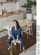 Купить «Beautiful woman in denim overalls sits on a chair in the kitchen.», фото № 30487523, снято 18 марта 2019 г. (c) Женя Канашкин / Фотобанк Лори