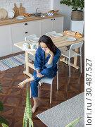 Купить «Beautiful woman sits in the kitchen and uses the phone.», фото № 30487527, снято 18 марта 2019 г. (c) Женя Канашкин / Фотобанк Лори