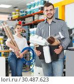 Купить «Glad couple showing tools for house decoration», фото № 30487623, снято 17 мая 2018 г. (c) Яков Филимонов / Фотобанк Лори