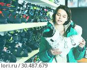 Купить «Smiling young female looking for new ski boots in ski equipment shop», фото № 30487679, снято 6 февраля 2018 г. (c) Яков Филимонов / Фотобанк Лори
