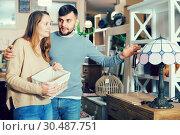 Купить «Couple choosing table lamp», фото № 30487751, снято 9 ноября 2017 г. (c) Яков Филимонов / Фотобанк Лори