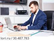 Купить «Confident man administrator of furniture store using laptop at workplace in showroom», фото № 30487783, снято 9 апреля 2018 г. (c) Яков Филимонов / Фотобанк Лори