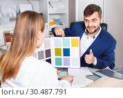 Купить «Competent seller in showroom helping young female client to choose furniture materials for her apartment», фото № 30487791, снято 9 апреля 2018 г. (c) Яков Филимонов / Фотобанк Лори