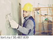 Купить «Workman in the helmet is plastering the wall», фото № 30487839, снято 3 июня 2017 г. (c) Яков Филимонов / Фотобанк Лори
