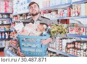 Купить «Tired male with heavy shopping basket», фото № 30487871, снято 20 января 2018 г. (c) Яков Филимонов / Фотобанк Лори