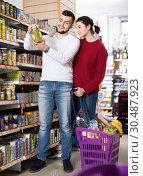 Купить «Couple standing near shelves with canned goods at store», фото № 30487923, снято 14 марта 2017 г. (c) Яков Филимонов / Фотобанк Лори