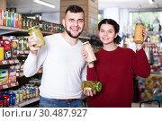 Купить «joyous young family choosing purchasing canned food for week at supermarket», фото № 30487927, снято 14 марта 2017 г. (c) Яков Филимонов / Фотобанк Лори