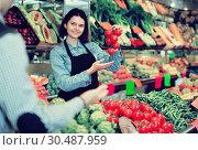 Купить «Seller helping customer to buy vegetables», фото № 30487959, снято 18 марта 2017 г. (c) Яков Филимонов / Фотобанк Лори