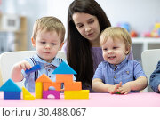 Купить «Preschool teacher and cute kids play in kindergarten», фото № 30488067, снято 7 июня 2020 г. (c) Оксана Кузьмина / Фотобанк Лори