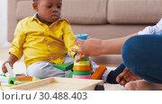 Купить «mother and baby playing with toy blocks at home», видеоролик № 30488403, снято 24 марта 2019 г. (c) Syda Productions / Фотобанк Лори