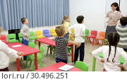 Купить «Portrait of schoolchildren with teacher performing daily physical exercises in classroom during break on lesson», видеоролик № 30496251, снято 30 января 2019 г. (c) Яков Филимонов / Фотобанк Лори