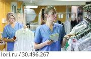 Купить «Two female dry-cleaning salon employees in process of work», видеоролик № 30496267, снято 11 февраля 2019 г. (c) Яков Филимонов / Фотобанк Лори