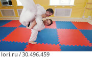 Martial arts. Two athletic men training their aikido skills in the studio. Throwing the opponent on the floor and producing strangulation. Стоковое видео, видеограф Константин Шишкин / Фотобанк Лори