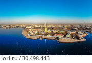Купить «Beautifull aerial view of the Petropavlovsky fortress in sunny spring day. Golden tall spire of famous Peter and Paul Cathedral on the blue sky background. Historical centre of St. Petersburg, Russia.», фото № 30498443, снято 4 апреля 2019 г. (c) Алексей Ширманов / Фотобанк Лори