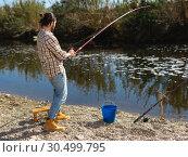 Купить «Adult man standing near river and pulling fish expressing emotions of dedication», фото № 30499795, снято 15 марта 2019 г. (c) Яков Филимонов / Фотобанк Лори