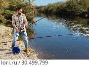 Купить «Adult man standing near river and pulling fish expressing emotions of dedication», фото № 30499799, снято 15 марта 2019 г. (c) Яков Филимонов / Фотобанк Лори