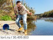 Купить «Adult man standing near river and pulling fish expressing emotions of dedication», фото № 30499803, снято 15 марта 2019 г. (c) Яков Филимонов / Фотобанк Лори