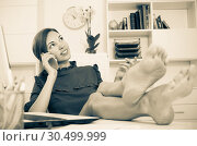 Купить «attractive female employee answering on phone and sitting with legs on working table at office», фото № 30499999, снято 7 июня 2020 г. (c) Яков Филимонов / Фотобанк Лори