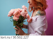 Gentle pink roses in the hands of a girl with a tattoo on a double pink blue background with copy space for text. Birthday present. Стоковое фото, фотограф Ярослав Данильченко / Фотобанк Лори