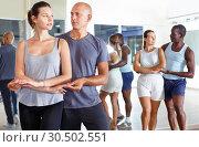 Купить «Young smiling people practicing passionate samba in dance class», фото № 30502551, снято 30 июля 2018 г. (c) Яков Филимонов / Фотобанк Лори