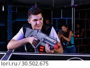 Купить «Excited guy holding laser pistol and playing laser tag with his friends», фото № 30502675, снято 27 августа 2018 г. (c) Яков Филимонов / Фотобанк Лори