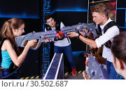 Купить «Two emotional players standing opposite each other with laser pistols in laser tag room», фото № 30502687, снято 27 августа 2018 г. (c) Яков Филимонов / Фотобанк Лори