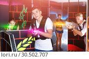 Купить «Portrait of excited guy with laser pistol playing laser tag in a», фото № 30502707, снято 27 августа 2018 г. (c) Яков Филимонов / Фотобанк Лори