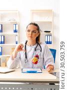 Купить «Young female doctor cardiologist sitting at the hospital», фото № 30503759, снято 5 ноября 2018 г. (c) Elnur / Фотобанк Лори