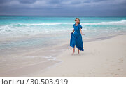 Купить «The woman in a long blue dress goes on the sea coast Cayo Largo island, Cuba», фото № 30503919, снято 1 февраля 2013 г. (c) Куликов Константин / Фотобанк Лори