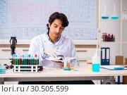 Купить «Young chemist working in the lab», фото № 30505599, снято 19 октября 2018 г. (c) Elnur / Фотобанк Лори
