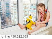 Купить «Russia, Samara, March 2017: A little girl is sitting with a plush dog on the windowsill of a high-rise building. Danger.», фото № 30522655, снято 14 марта 2017 г. (c) Акиньшин Владимир / Фотобанк Лори