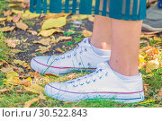 Купить «Women's legs in sports white sneakers on autumn leaves.», фото № 30522843, снято 16 сентября 2018 г. (c) Акиньшин Владимир / Фотобанк Лори