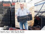 Купить «Man professional gardener holding crate with fertilization», фото № 30523623, снято 20 января 2020 г. (c) Яков Филимонов / Фотобанк Лори