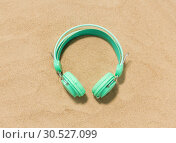 Купить «earphones on summer beach sand», фото № 30527099, снято 27 июня 2018 г. (c) Syda Productions / Фотобанк Лори