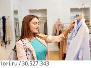 Купить «happy woman choosing clothes at clothing store», фото № 30527343, снято 19 февраля 2016 г. (c) Syda Productions / Фотобанк Лори