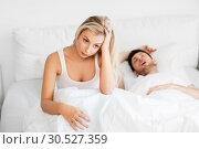 unhappy woman in bed with snoring sleeping man. Стоковое фото, фотограф Syda Productions / Фотобанк Лори