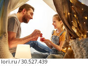 Купить «family playing tea party in kids tent at home», фото № 30527439, снято 27 января 2018 г. (c) Syda Productions / Фотобанк Лори