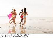 Купить «friends run with beach ball and swimming mattress», фото № 30527507, снято 29 июля 2018 г. (c) Syda Productions / Фотобанк Лори
